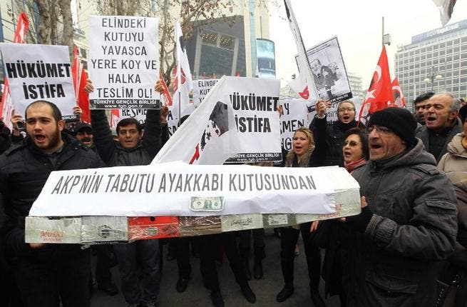 People shout anti-government slogans as they carry a casket made of empty shoe boxes during a protest against corruption in Ankara, on December 21, 2013. [AFP]