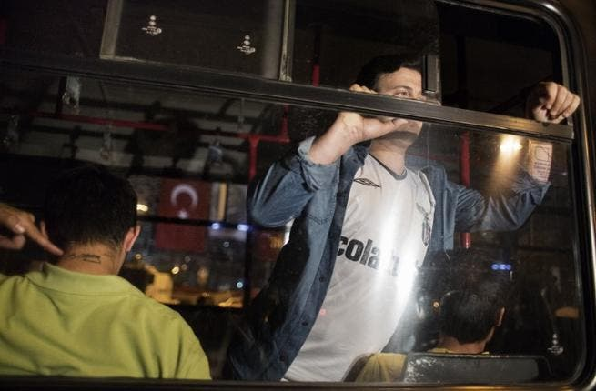 Men detained for emulating Turkish choreographer Erdem Gunduz for standing on Taksim square in a lone protest are seen arrested inside a truck used by the Turkish police June 18 (Marco Longari / AFP)