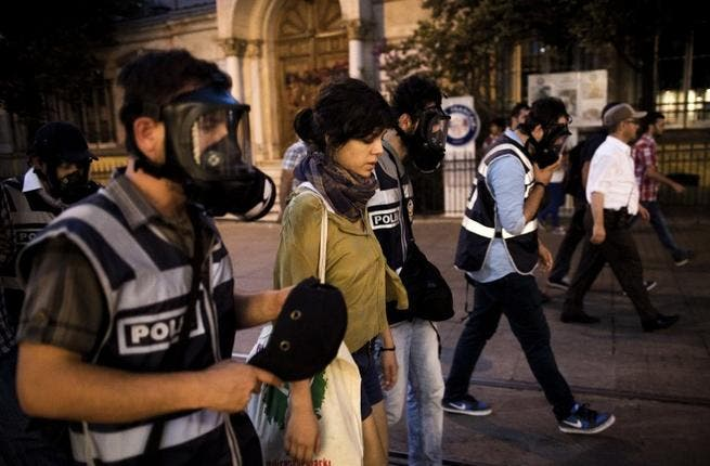 Turkish policeman detain a protestor during a protest on Istiklal Avenue in Istanbul on July 8 (AFP)