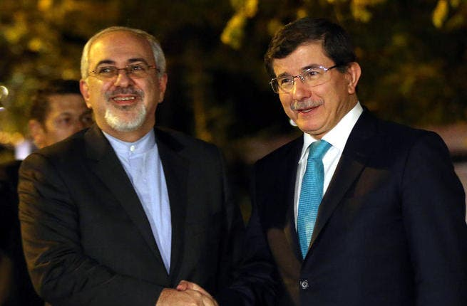 Turkish Foreign Minister Ahmet Davutoglu (R) shakes hands with his Iranian counterpart Javad Zarif prior to a meeting in Ankara. (Image credit: AFP)