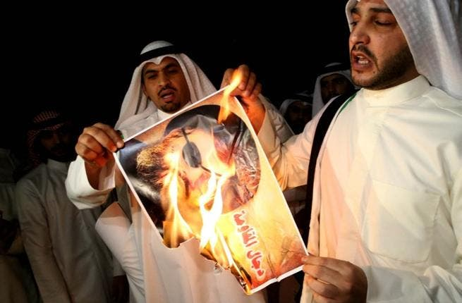 Kuwaiti protesters set ablaze a picture of Lebanese Shiite movement Hezbollah's chief Hassan Nasrallah during a protest in front the Lebanese embassy against Hezbollah's and Iran's involvement in Syria, in Kuwait city on June 11 (Yasser al-Zayyat / AFP)