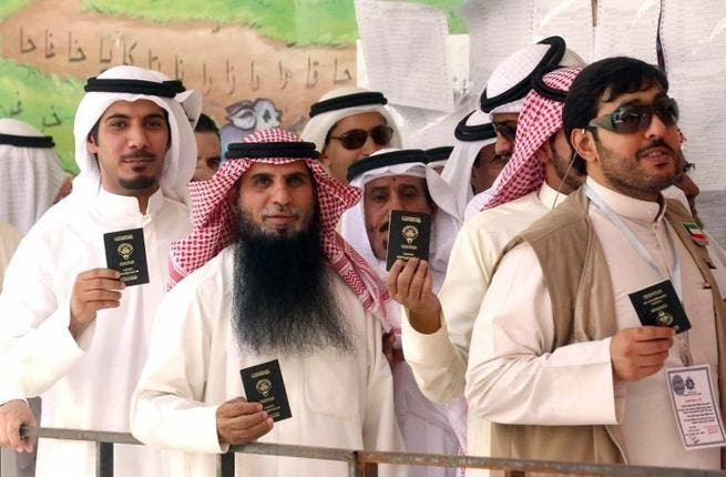 Kuwaiti men display their identity cards as they wait to cast their votes at a polling station in Kuwait City on July 27, 2013. (AFP/YASSER AL-ZAYYAT)