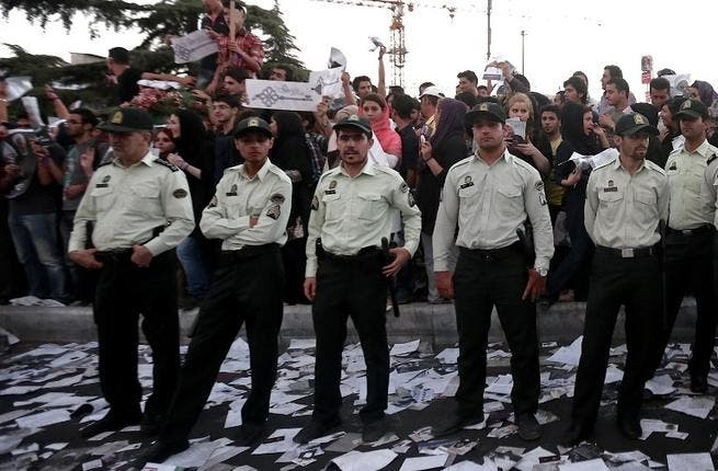 Iranian policemen stand guard as supporters of Iranian moderate presidential candidate, Hassan Rowhani, attend a street rally at Vanak square in northern Tehran on June 12 (Behrouz Mehri / AFP)