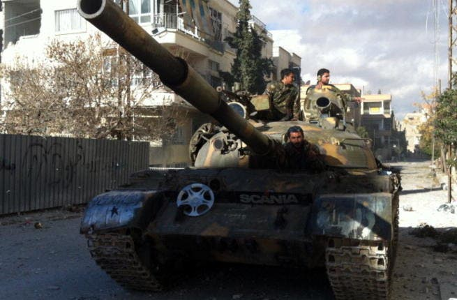 Syrian pro-government forces patrol in their tank in the town of Nabak near Damascus on December 7, 2013. [Getty Images]