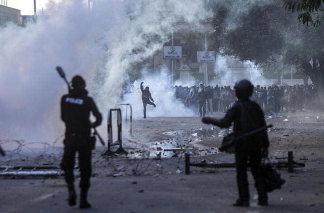 Egyptian students who support the Muslim Brotherhood (background) clash with riot policemen outside the University of Cairo campus in the capital on December 11, 2013. [AFP]