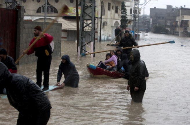 Palestinian civil defense volunteers help people to travel across flood waters in Gaza City following rain storms for the past few days, on December 14, 2013. [Getty Images]