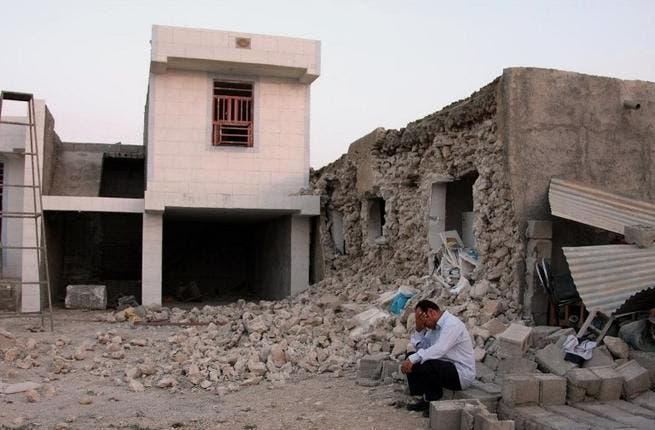 A man squats outside his destroyed home in Shonbeh, after the Bushehr earthquake (AFP)