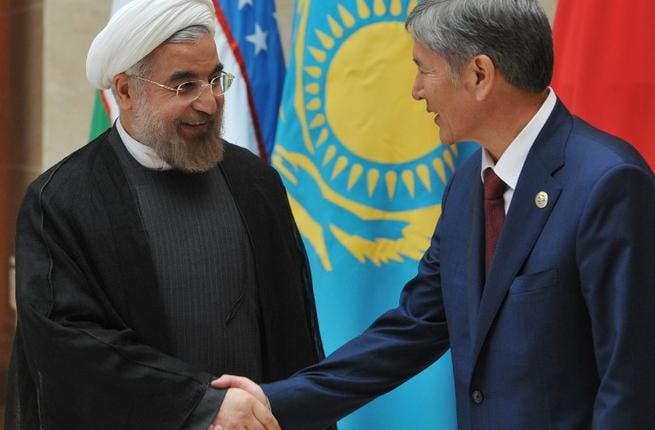 Kyrgyzstan's President Almazbek Atambayev shows the way to his Iranian counterpart Hassan Rowhani at a summit of the Shanghai Cooperation Organization. [AFP]