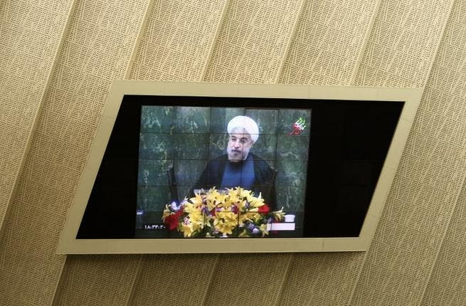 IRAN, Tehran : Iranian President Hassan Rowhani is seen on a TV screen as he speaks during a parliament session to elect the cabinet members on August 15, 2013. AFP PHOTO/BEHROUZ MEHRI