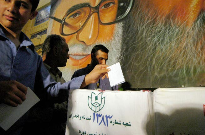 Iranian men cast their ballots beneath a poster of Ayatollah Ali Khamenei during the Iranian presidential election. (Image credit: Getty)