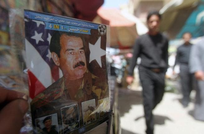 A man holds a CD with a photo of former Iraq President Saddam Hussein (AFP/Ahmad Al Rubaye)