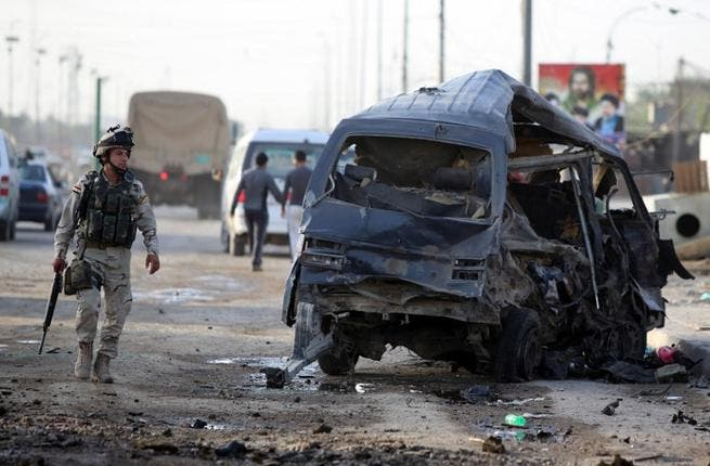 An Iraqi soldier inpects the remains of a vehicle at the scene of a car bomb explosion the previous days in Baghdad's Sadr City district on May 16, 2013 (Ahmad al-Rabaye/ AFP)
