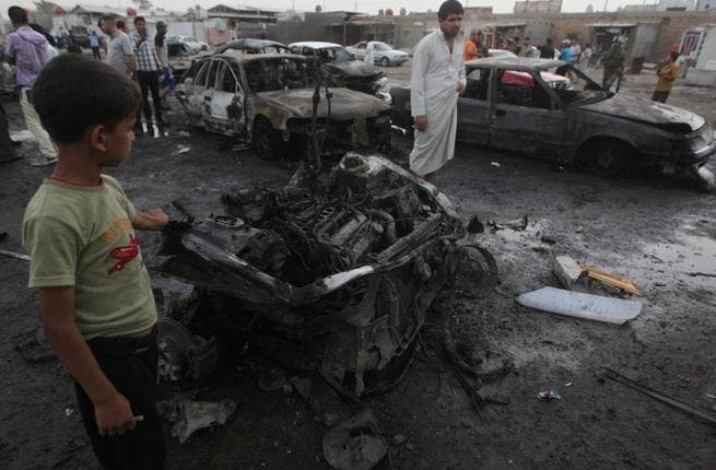 Iraqis gather at the scene of one of the two car bombs that exploded near an used car dealerships in Baghdad's Habibiyah area on May 27(Ahmad Al-Rubaye/ AFP)