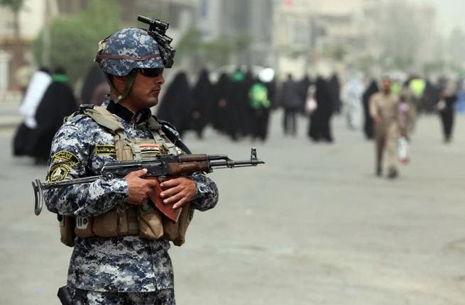 An Iraqi soldier stands guard on a main road in Baghdad as Shiite Muslim pilgrims arrive on June 2 (Ahamd al-Rubaye / AFP)