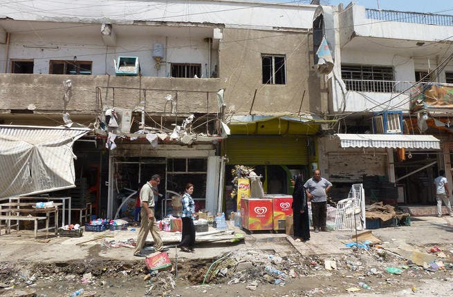 Iraqis inspect the damage outside shops in Baghdad on June 25, 2013 following an explosion the night before (Sabah Arar / AFP)