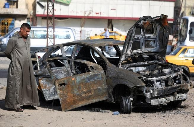 An Iraqi man inspects a burnt-out vehicle at the site of a car bomb explosion in the Hurriyah area of eastern Baghdad (Ahmad Al-Rubaye / AFP)