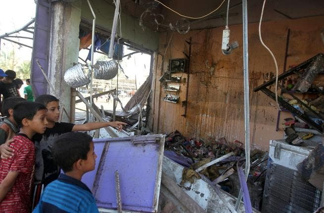Children look at the damage following a car bomb in the Shuala area of eastern Baghdad, on July 3, 2013, following several attacks the previous day (AFP)