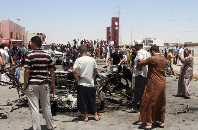 Iraqis inspect the site of a suicide car bomb attack in the Al-Haq square in Samarra, a predominantly Sunni town north of Baghdad, on July 5 (AFP)