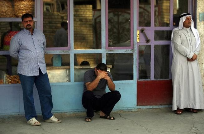 Iraqi men react to the death of family members in the Dora area of south Baghdad (Ahmad al-Rubaye / AFP)