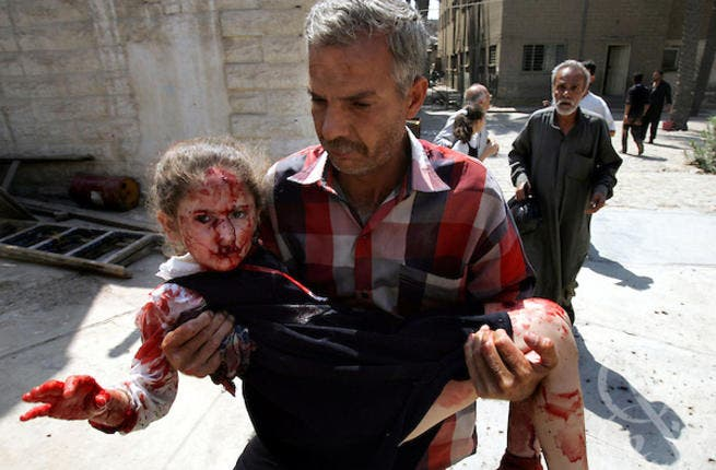 Man carries child from school bombing rubble. [photoshelter]