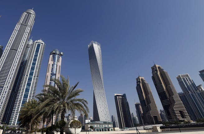 The Cayan tower (C), the world's tallest twisted tower stands at Dubai's Marina on June 11, 2013 in the United Arab Emirates, UAE. (AFP/KARIM SAHIBSAHIB)