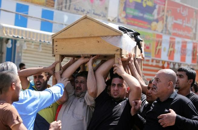 Iraqis carry the coffin of one of the victims of the attack on a Shiite mosque. [AFP]