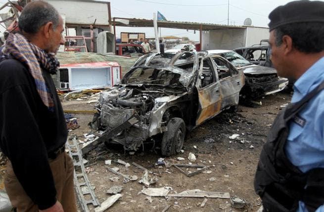 An Iraqi policeman and civilian inspect the wreckage of a car bomb in Baghdad on April 15 (AFP/ Ahmad Al Rubaye)