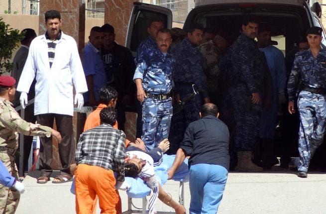 Iraqi medics wheel a man to hospital after demonstrators and security forces near Kirkuk (Marwan Ibrahim/AFP)