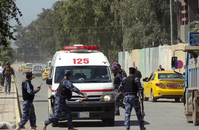 Iraqi soldiers surround an ambulance after deadly clashes at a Sunni protest camp in Hawija, near Kirkuk