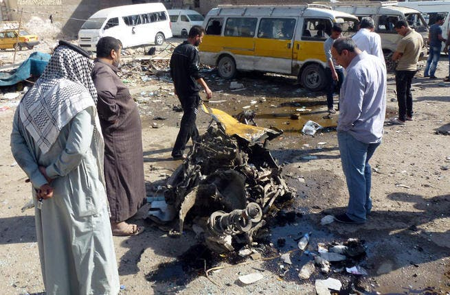 Iraqis look at the remains of a vehicle following an explosion at a small bus station . (Image credit: AFP)