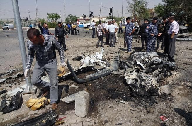 IRAQ, Kirkuk : Iraqi policemen and investigators inspect the remains of a car bomb that exploded outside the ministry of education in the northern Iraqi city of Kirkuk on August 22, 2013. AFP PHOTO MARWAN IBRAHIM
