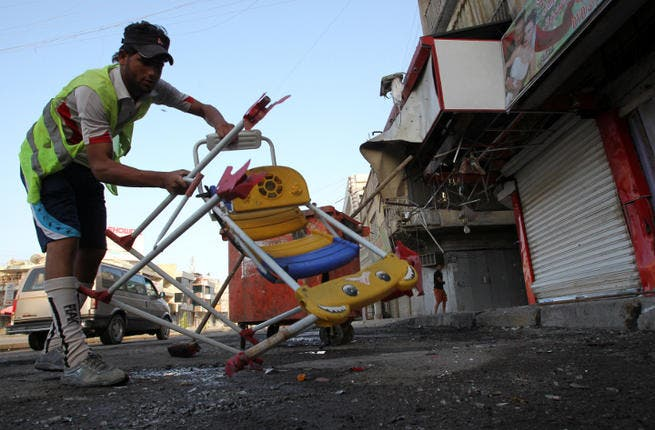 An Iraqi worker removes chairs as he cleans the site of a car bomb attack. (Image credit: AFP)