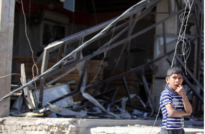 An Iraqi boy stands at the site the morning after a car bomb attack. (Image credit: AFP)