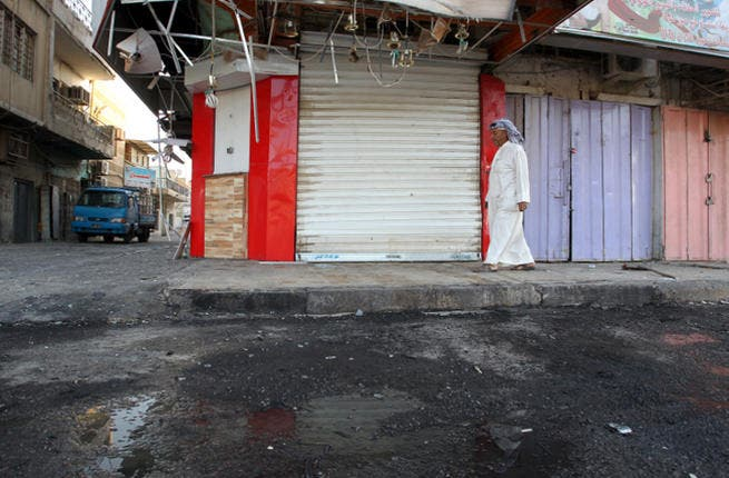 An Iraqi walks on the site of a car bomb that exploded outside a restaurant. (Image credit: AFP)
