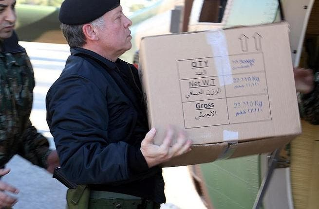 King Abdullah of Jordan loading a box containing ready meals onto a helicopter during his visit to the Northern Command in Ajloun, as he follows up on the national effort to deliver services and goods to citizens caught in the snow storms through out the kingdom. [AFP]