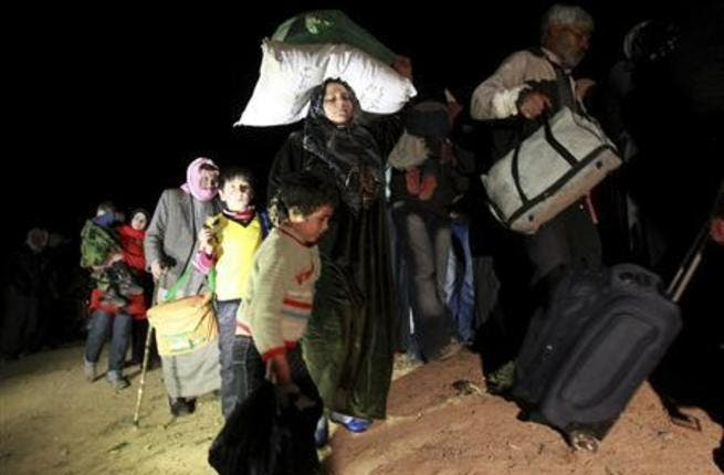 In darkness, Syrian refugees stream across country borders. [Reuters]