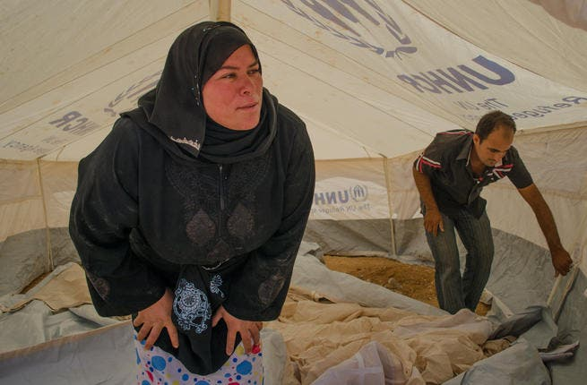 Scoping out the new home: Two new arrivals to the Zaatari camp inspect the tent that will be their humble abode. (AlBawaba/J. Zach Hollo)