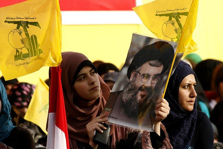 A woman holds a photo of Hizbollah leader Hassan Nasrallah (Source: AFP file photo)