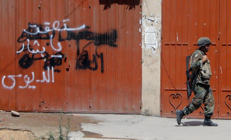 A Lebanese soldier walks past anti-Assad graffiti in the northern city of Tripoli (AFP)