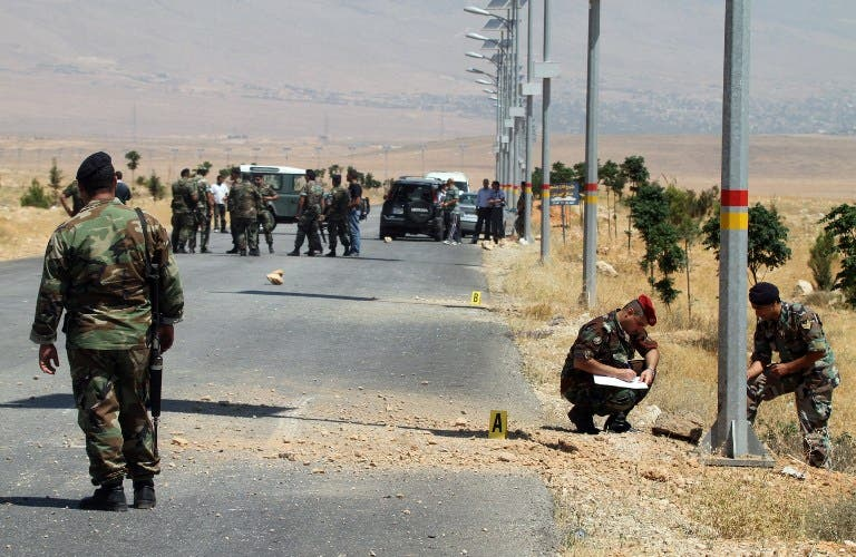 Lebanese army soldiers inspect the site of twin roadside bombs, detonated minutes apart, in the town of Hermel, a few kilometres from Baalbek in the Bekaa valley (AFP)