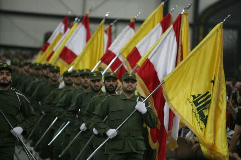 LEBANON, Beirut : A picture taken on November 11, 2009, shows Hezbollah fighters, holding up Lebanese flags and the yellow flag of the militant Shiite Muslim group, as they parade on the occasion of Martyr's Day in the southern suburbs of Beirut.  AFP PHOTO/RAMZI HAIDAR