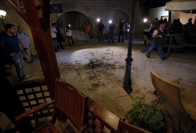 LEBANON, BAABDA : Journalists inspect the damage at a private residence where one of two rockets fired from an unknown location exploded in the early hours of August 2, 2013, just metres from an entrance to the presidential palace in Baabda. AFP PHOTO / ANWAR AMRO
