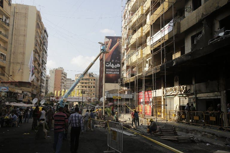 LEBANON, Beirut : Workers from Jihad al-Binaa, a construction company affiliated with the Shiite Muslim Hezbollah movement, clear up the neighbourhood where a car bomb exploded the previous week in a southern Beirut stronghold of the pro-Syria Shiite group on August 19, 2013.  AFP PHOTO/JOSEPH EID