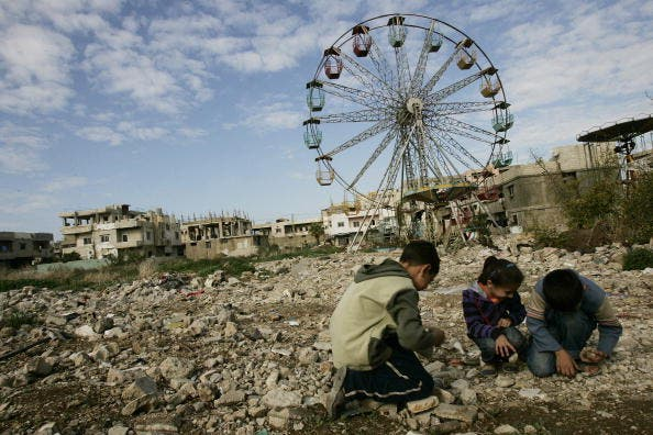 Palestinian children collect stones to be thrown at their friends as they play a 'war' game in the Palestinian refugee camp of Nahr al-Bared, 2009.  JOSEPH EID/AFP/Getty Images)