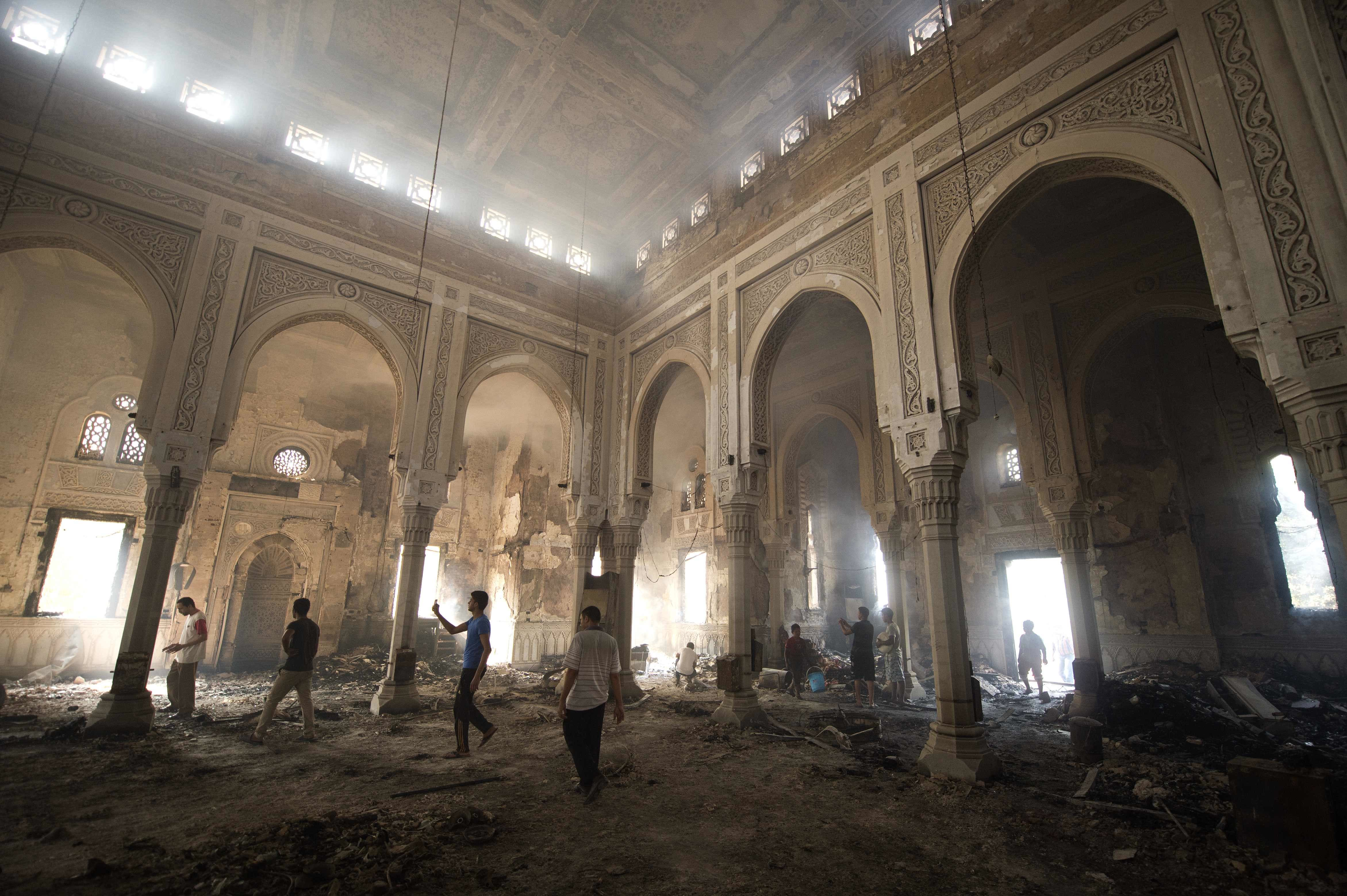 Residents walk through debris and rubble inside the burnt-down mosque of Rabaa al-Adawiya (AFP/KHALED DESOUKI)