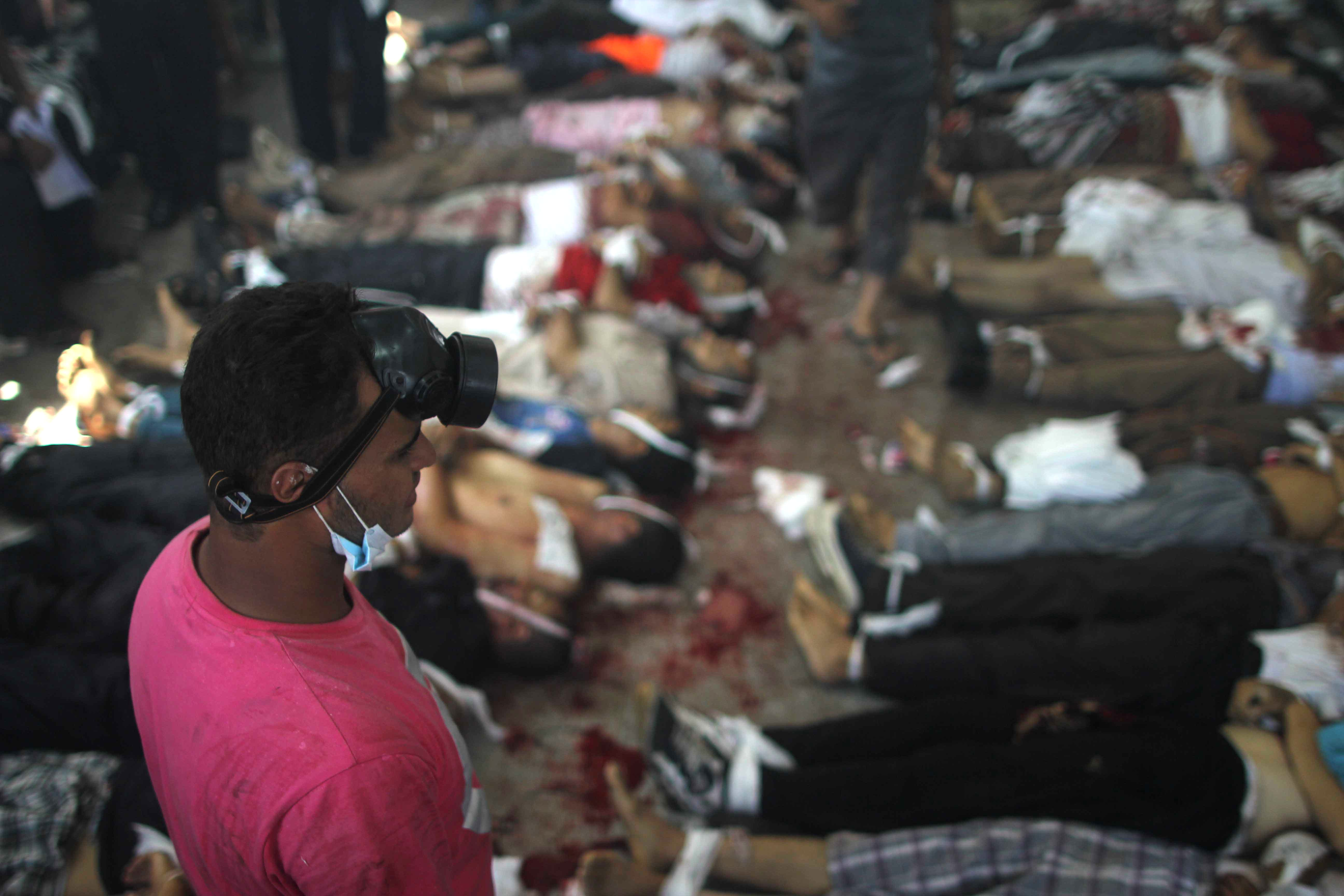 A man looks at bodies laid out in a make shift morgue after Egyptian security forces stormed two huge protest camps at the Rabaa al-Adawiya and Al-Nahda squares where supporters of ousted president Mohamed Morsi were camped (AFP/MOSAAB EL-SHAMY)