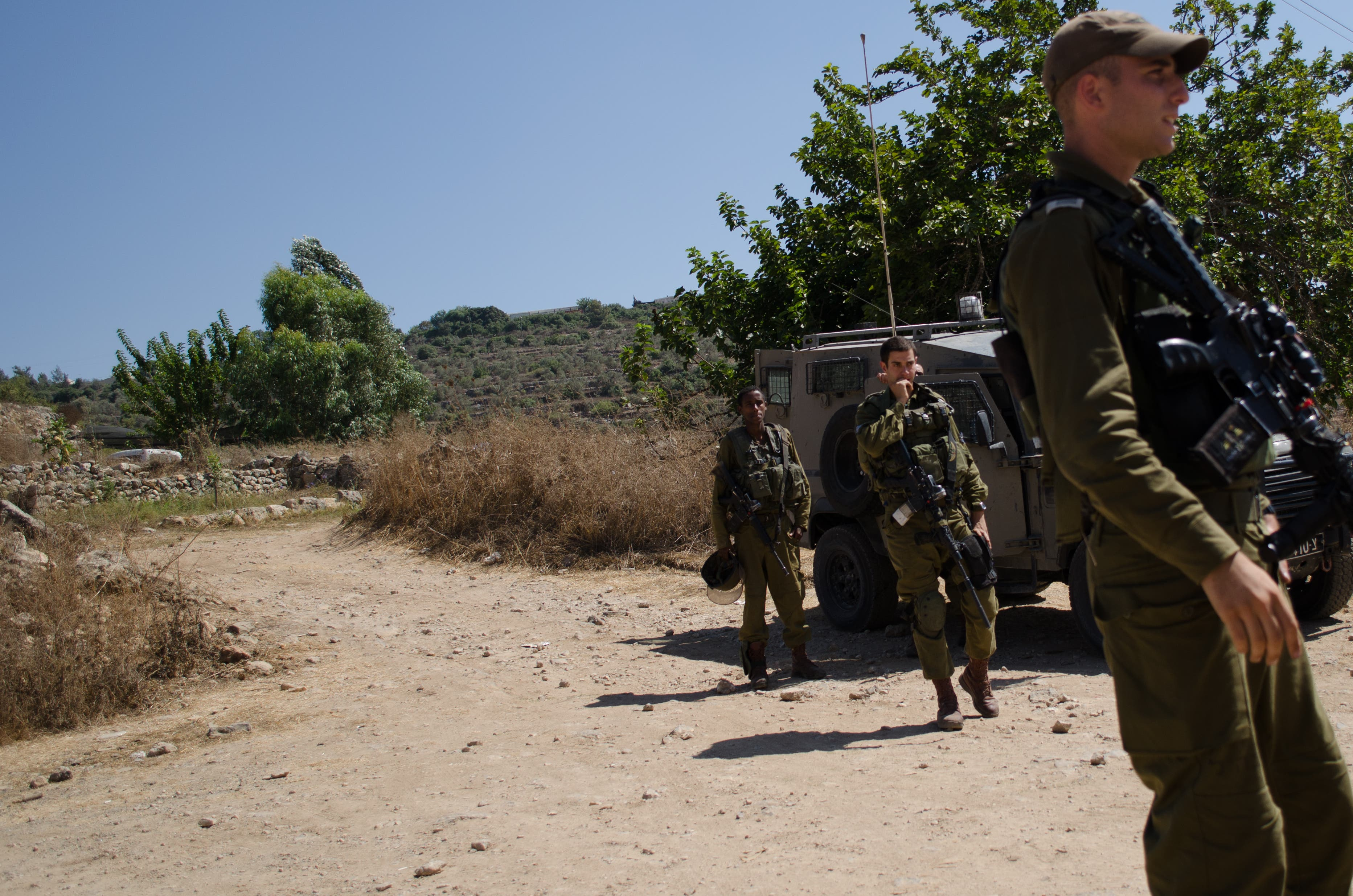 Israeli Defense Forces stand guard in front of the entrance to Ein al-Qaws Spring, which previously served as Nabi Salih's water source for agriculture. Since the spring's seizure, crops in the village have have been dying. (Albawaba/J. Zach Hollo)