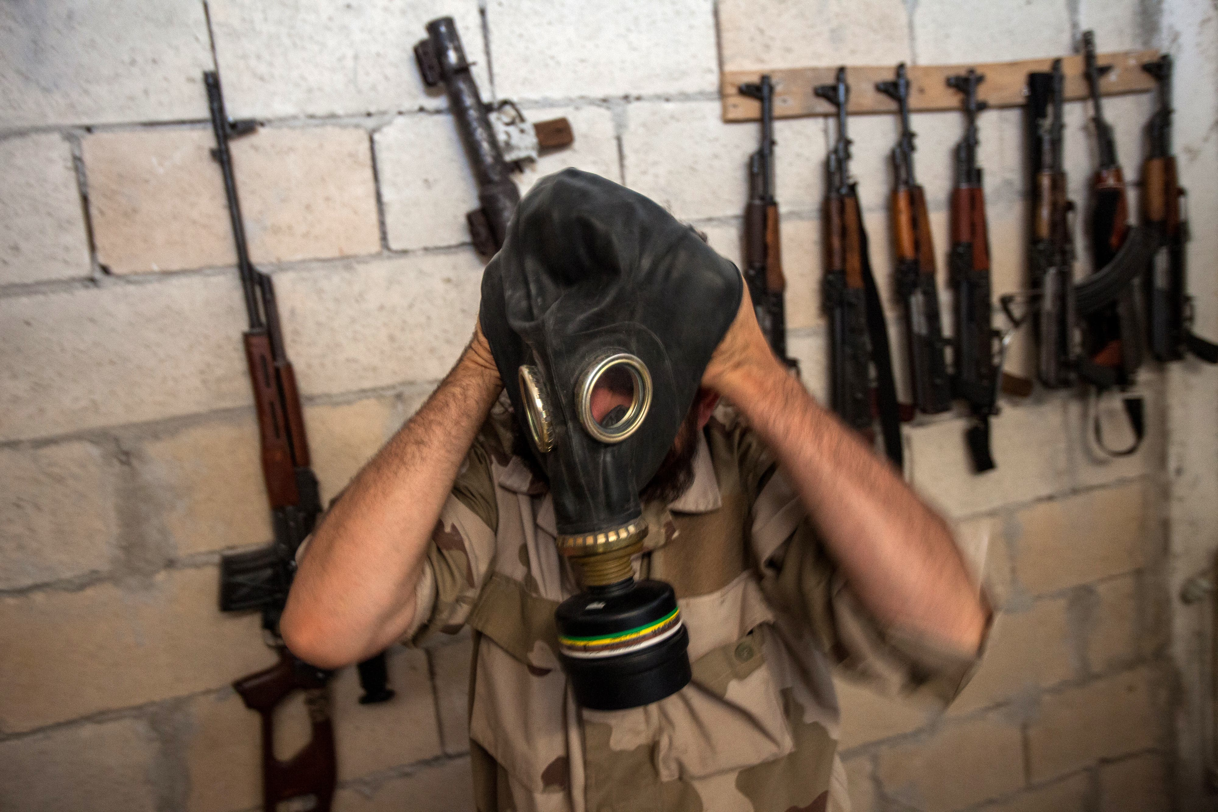 A Syrian rebel tries on a gas mask seized from a Syrian army factory in the northwestern province of Idlib (AFP/DANIEL LEAL-OLIVAS
