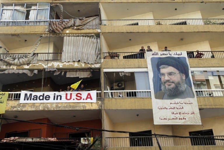 LEBANON, Beirut : Lebanese people hand a poster of Hassan Nasrallah, the head of Lebanon's militant Shiite Muslim movement Hezbollah, from their balcony. AFP PHOTO / ANWAR AMRO