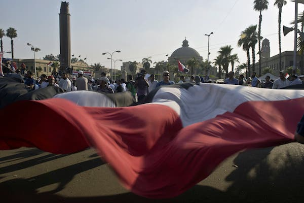 Egyptian supporters of President Mohamed Morsi wave a large national flag during a rally outside Cairo University (Source: AFP/KHALED DESOUKI)